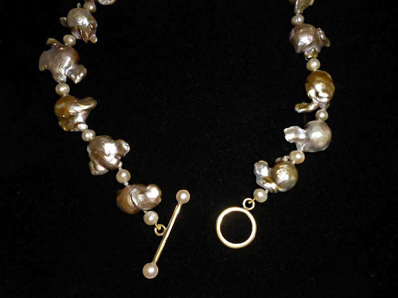9CT GOLD, T-BAR AND RING FASTENING ON A STRING OF FRESHWATER PEARLS